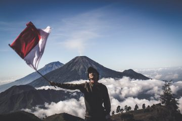 man wearing black crew neck sweater holding white and red flag standing near mountain under blue and white sky